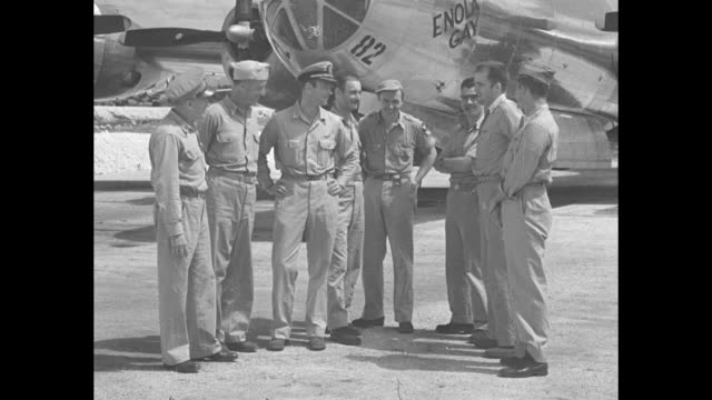 CU nose of US B29 military airplane with name 'Enola Gay' / crew of 'Enola Gay' stands in front of plane with members of the Manhattan Project and...