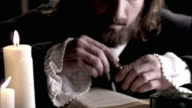 Nostradamus removes the stopper from a vial and reads a book by candlelight.