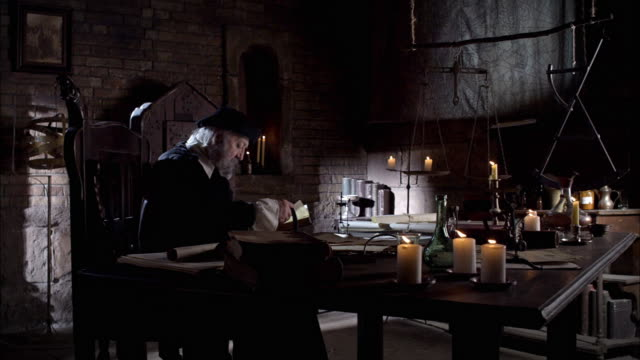Nostradamus sits at a desk and reads by candlelight.