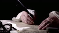 Nostradamus uses a quill to make notes on a parchment.