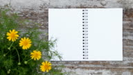 Notepad wood table and flowers