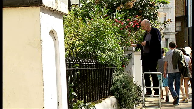 Notting Hill Carnival family day Man tending to plants in his front garden as standing on stepladder Vox pops SOT