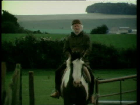 Novelist William Golding riding horse in field in Wiltshire Oct 83