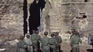 November 1942 TU A squad of US Army soldiers and a drum and bugle unit marching into the ruins of a Vichy French fort in the aftermath of Operation...