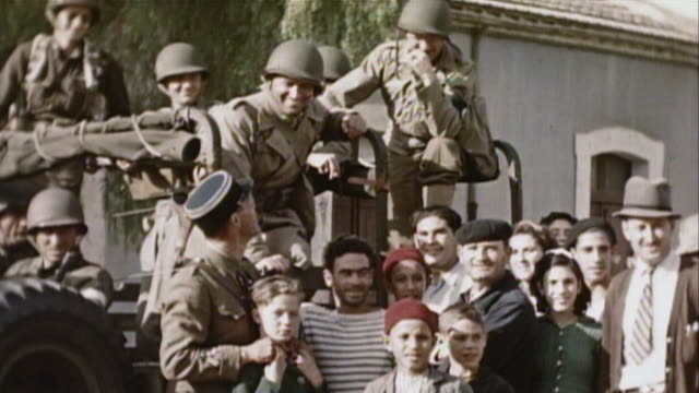 November 1942 MS US Army soldiers aboard a Jeep and a Vichy French soldier posing with civilians including children on the street after Operation...