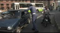 November 2 2005 WS Policeman stopping and rerouting vehicles and motorcyclists on busy Lahore street / Pakistan