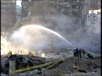 November 6 2001 MONTAGE Ground Zero clean up operations with firemen spraying the debris and a backhoe digging / New York City New York United States