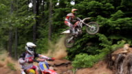 November 9 2009 MONTAGE Two professional motocross riders driving off road at high speed and completing jumps through the woods