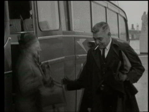 November LIB London EXT Gable and wife Kathleen Gable off BOAC airport coach with Clark Gable smoking cigarette / Couple past and pose for photocall...