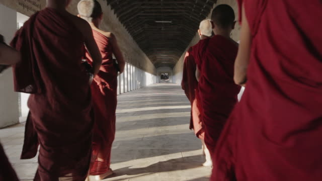 WS Novice Buddhist monks walk away from camera through a temple corridor with alms bowls / Bagan, Myanmar