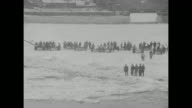 Number 3 boat struggling through ice on river / VS men pulling boats over ice / groups of men with boats in distance on ice floe / people watching...