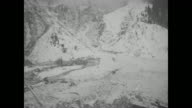 Numerous shots of partially snowcovered buildings and wreckage in valley with mountains beyond / as solemn villagers look on men dig in deep trench /...