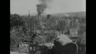 Numerous shots of smoldering devastated Nuremberg at close of European war / good shot of twin spires of St Sebaldus Church with American tank...