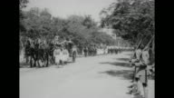 Numerous white horses followed by an elaborate carriage with liveried servants walking alongside / British High Commissioner George Lloyd and wife...