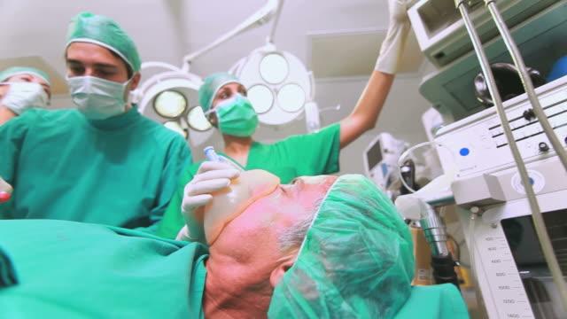 Nurse adjusting a monitor next to a patient