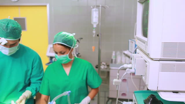 Nurse drying forehead of a concentrated surgeon