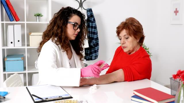 Nurse giving injection to senior woman
