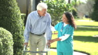 Nurse helping senior man using a walker outdoors