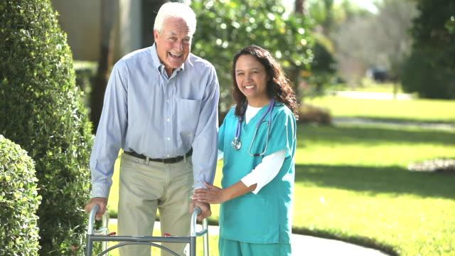 Nurse helping senior man using a walker outdoors