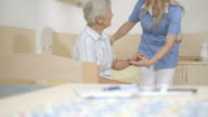 HD DOLLY: Nurse Helping Senior Woman To Stand Up