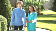Nurse helping senior woman using a walker outdoors