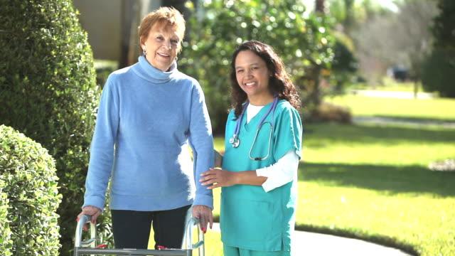 Nurse helping senior woman using a walker outdoors