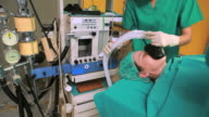 Nurse holding an oxygen mask above the head of patient