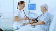 Nurse measuring a womans blood pressure
