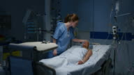 DS Nurse observing a female patient lying in the intensive care unit