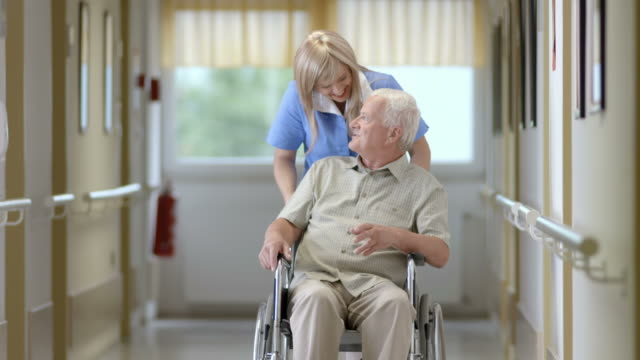 HD: Nurse Pushing Senior Man On Wheelchair