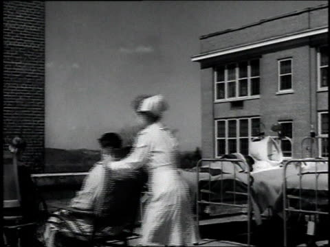 Nurse pushing tuberculosis patient in wheelchair to join other patients lying in hospital beds outside / United States