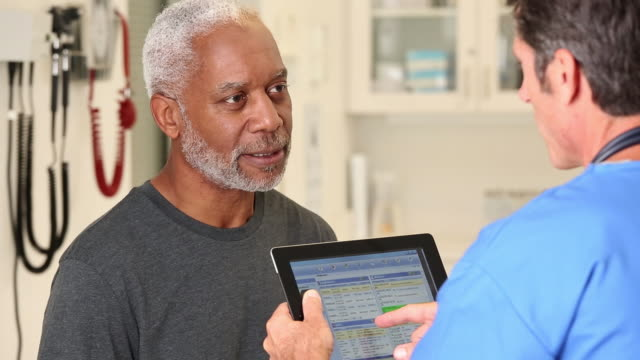 CU TU Nurse Reviewing Digital Patient Records with Senior Man / Richmond, Virginia, United States