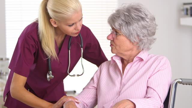 Nurse with concerned elderly patient in wheelchair