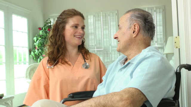 Nurse with Wheelchair Bound Male in Home