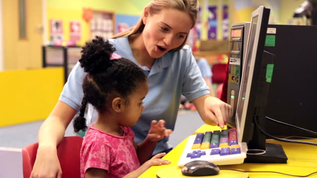 Nursery worker teaching child how to use a computer keyboard