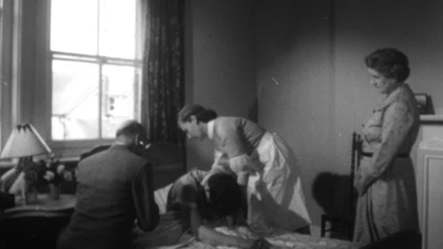 1955 MONTAGE Nurses and doctor making home visit for a patient with a serious condition / United Kingdom