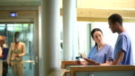 nurses checking notes in a hospital corridor