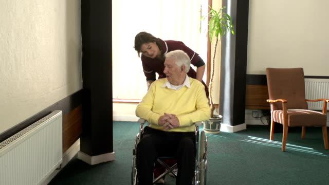 Nursing Care Home worker - Pushing elderly man in Wheelchair