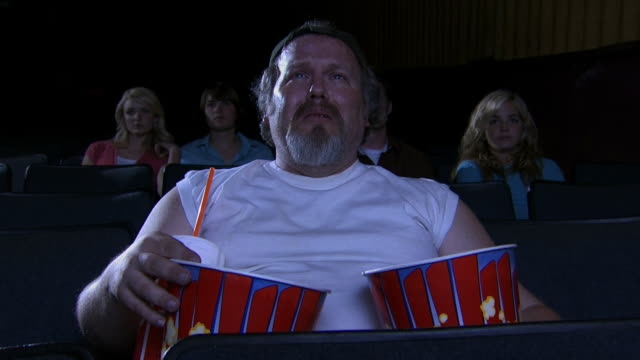 Obese man at movie theater eating popcorn and crying