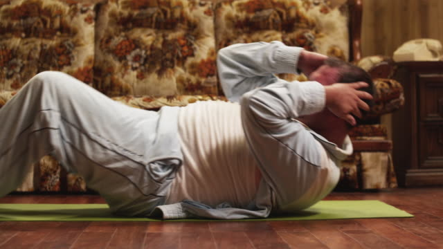 MS Obese man doing sit ups on living room floor / Orem, Utah, USA