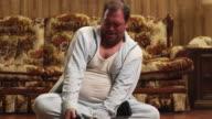 MS TD Obese man trying to sit in lotus pose in living room floor / Orem, Utah, USA