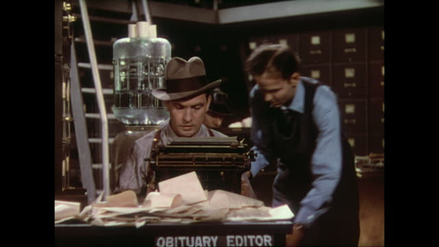 Obituary editor (Fredric March) is jostled and bumped as he works in busy press room