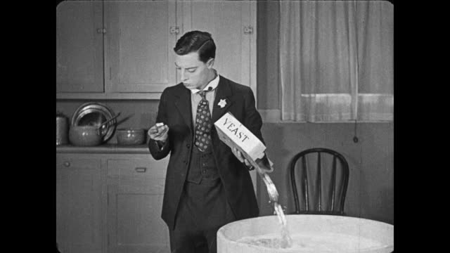 Oblivious Buster Keaton puts too much yeast in vat, which spills over filling room with bubbles of yeast