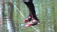 Obstacle racers across pond on wires requiring strength and balance