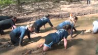 Obstacle racers crawl through mud pit under barbed wire