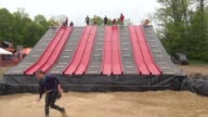 Obstacle racers down slide into muddy water Two shots good splashing