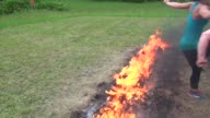 Obstacle racers jump over fire pit