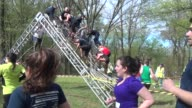 Obstacle racers over climbing structure with runners going by in foreground