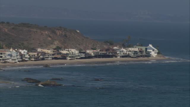AERIAL Ocean and beach and mountain and houses along the coast / Malibu, California, United States