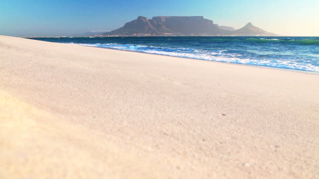 Ocean laps white beach Table Mountain